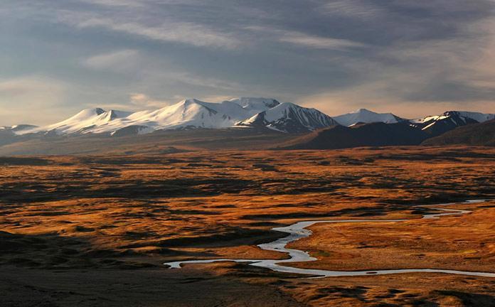 Заснеженные горные вершины над степью на реке Таван-Богдо-Ула Алтай, плато Укок, Россия.