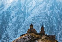 Древняя Троицкая церковь в Гергети (Гергетис Цминда Самеба) напротив ледника у подножья горы Казбек, Кавказ, Грузия.